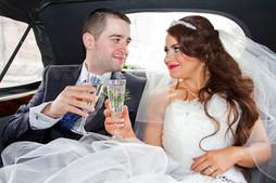 Bride & Groom raise a toast to each other in their car.  Kelvingrove Park, Glasgow