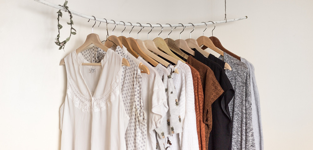 clothing rack with neutral toned clothes hanging