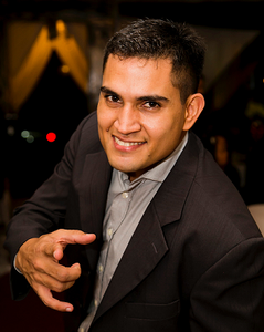 Man smiling in suit and pointing