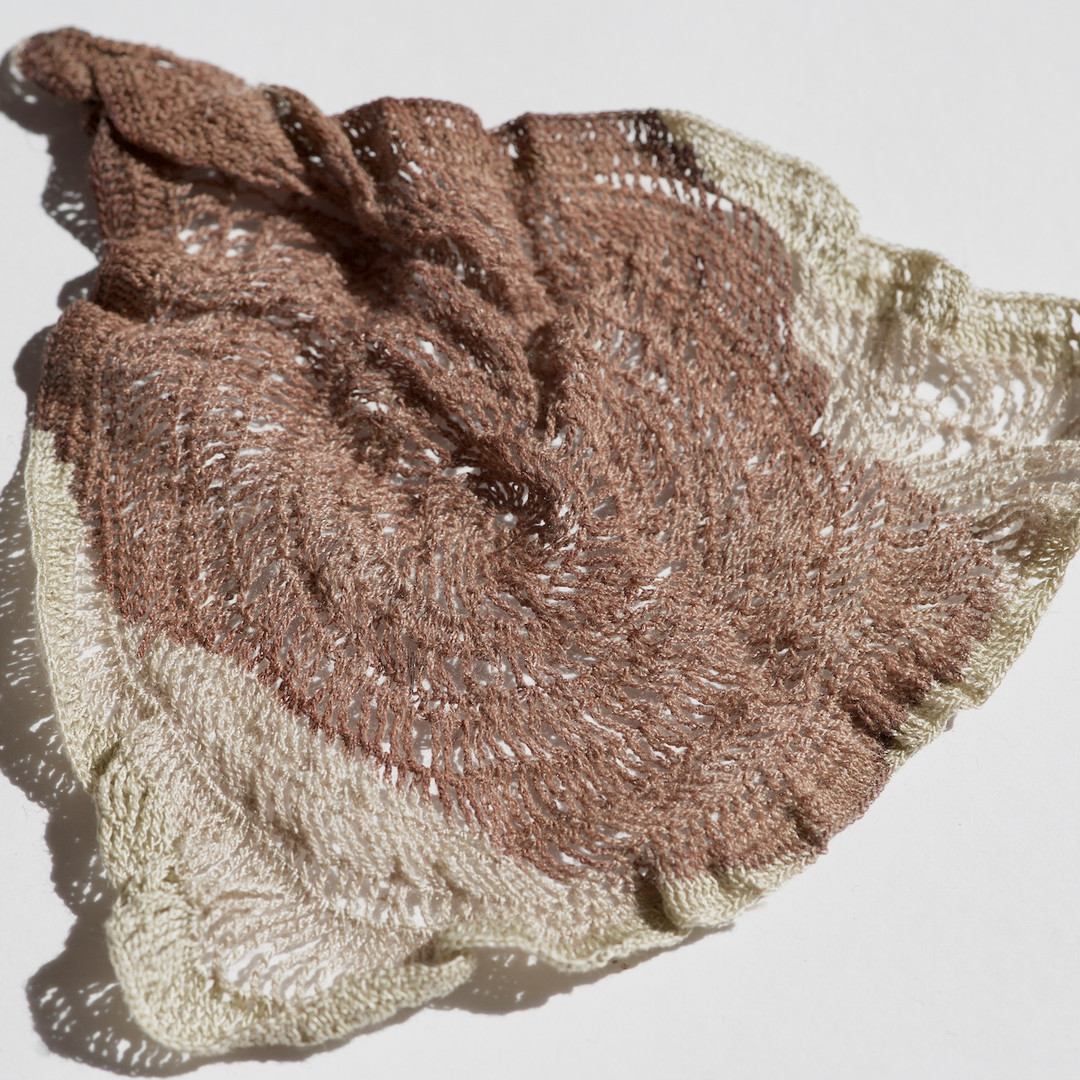 """a used triangular """"menstruation doily"""" with dried brown blood covering most of it's surface area. the crochet piece is slighly wrinkled and is made from off-white sewing thread."""