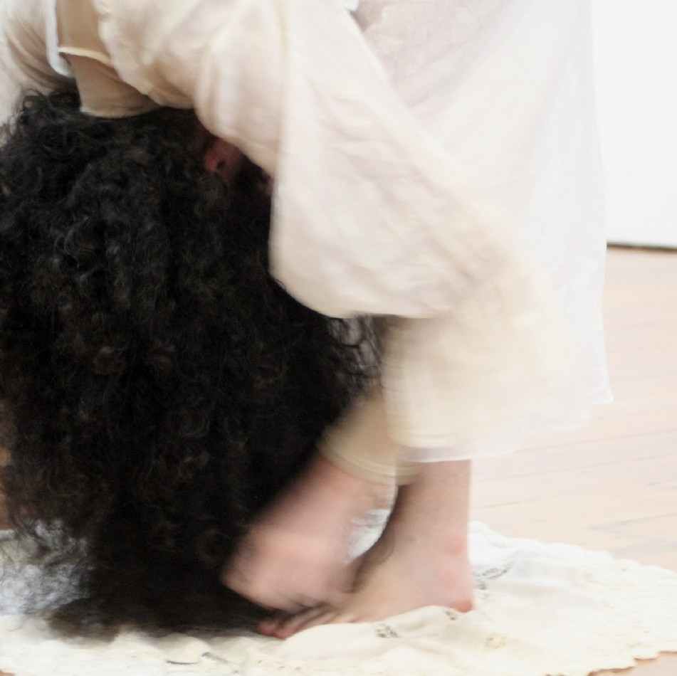 the artist stands while drying their feet with hair