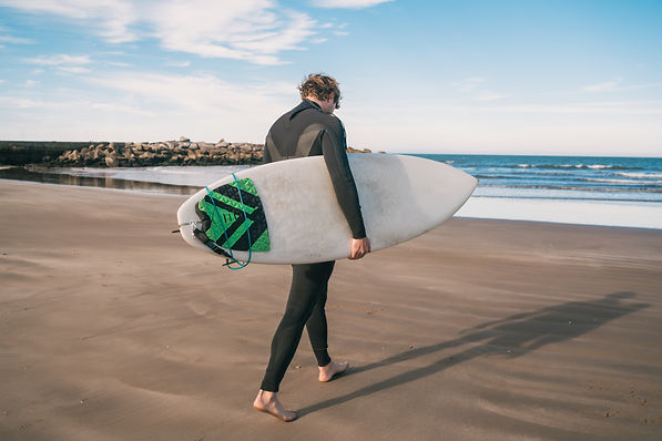 young-surfer-standing-in-the-ocean-with-his-surfboard-in-black-surfing-suit-sport-and-wate