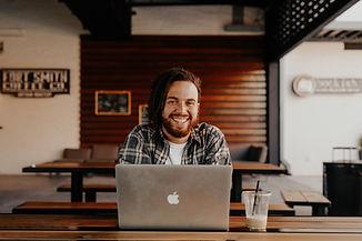 Man smailing behind laptop. Image by Brooke Cagle