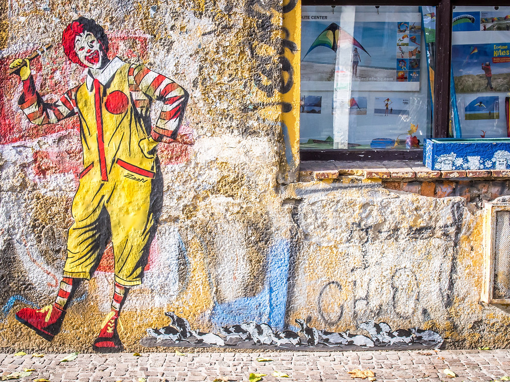 Graffiti on a wall showing Ronald McDonald playing a pipe with a line of rats following him