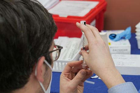 Person holding vaccine syringe