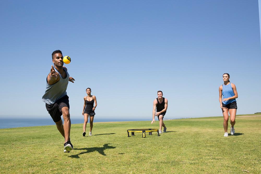 Adults playing spikeball.