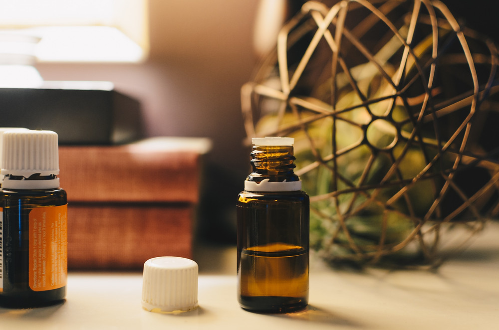 Open essential oil bottle on a desk, by Kelly Sikkema quit them