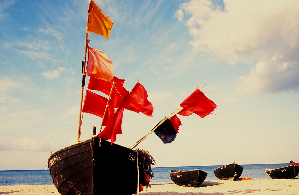 four fishing boats, one with red flags