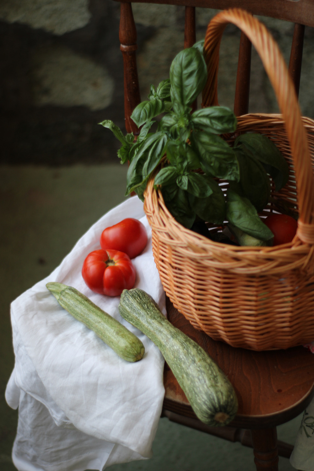 A basket of fresh basil sits on a chair next to fresh zucchini and tomatoes