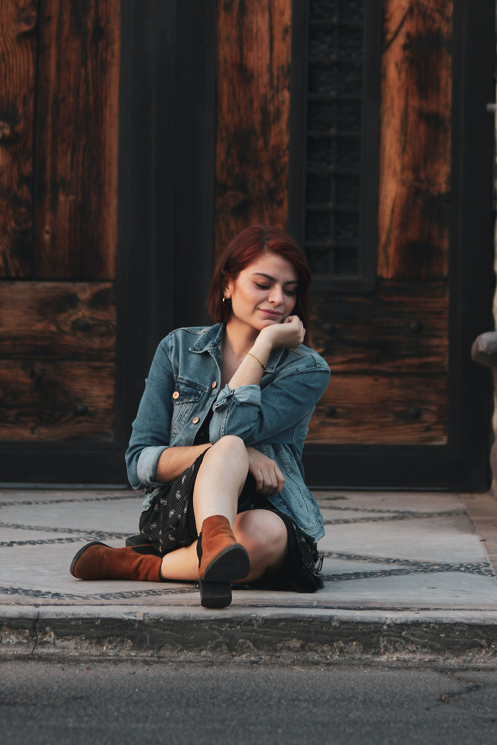 woman smiling and sitting on the ground with her leg out