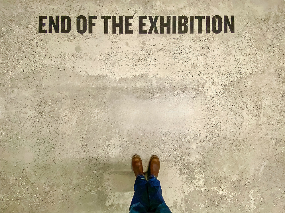 a man standing on a grey peice of land made from cement with teh words end of teh exhibition in front of him you can see his borwn shoes and blue jeans the man has taken the picture from above