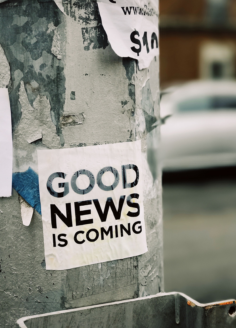 a note stuck to a metal post saying 'good news is coming'
