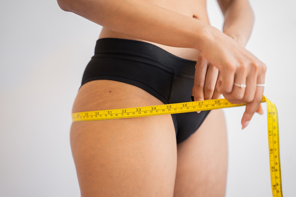 girl measuring hips for weight loss
