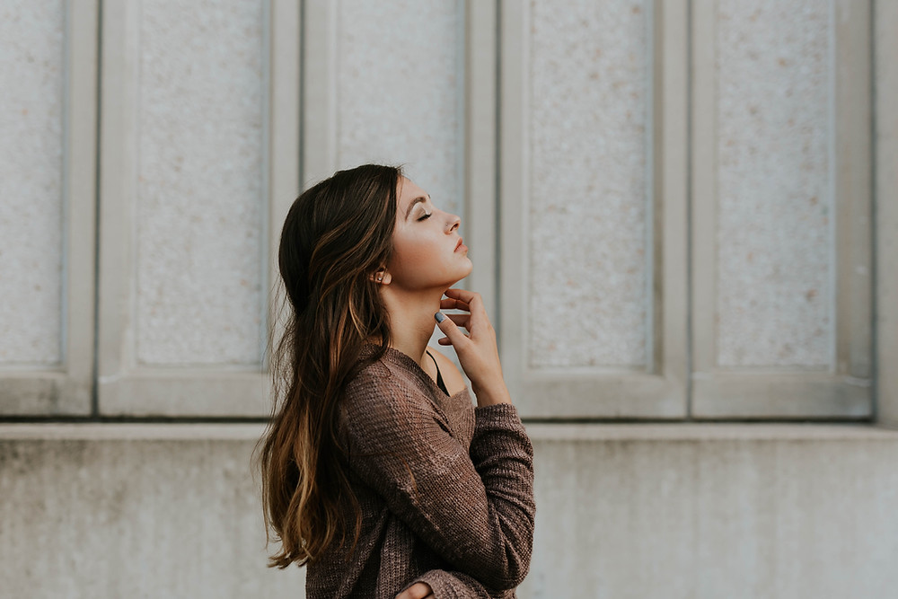 a woman leaning her head back and touching her neck Hypothyroidism: Answers to 7 Common  Questions