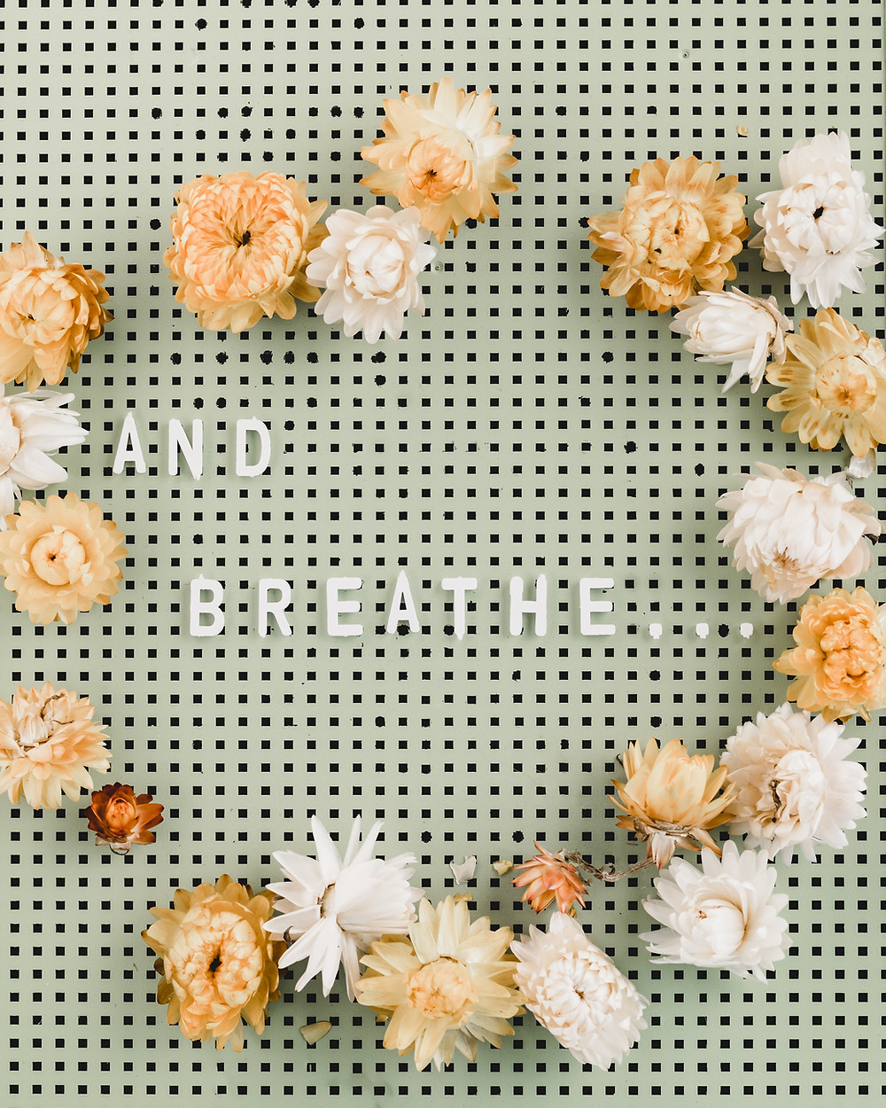 """pink flowers on a pegboard surrounding the text """"and breathe..."""""""