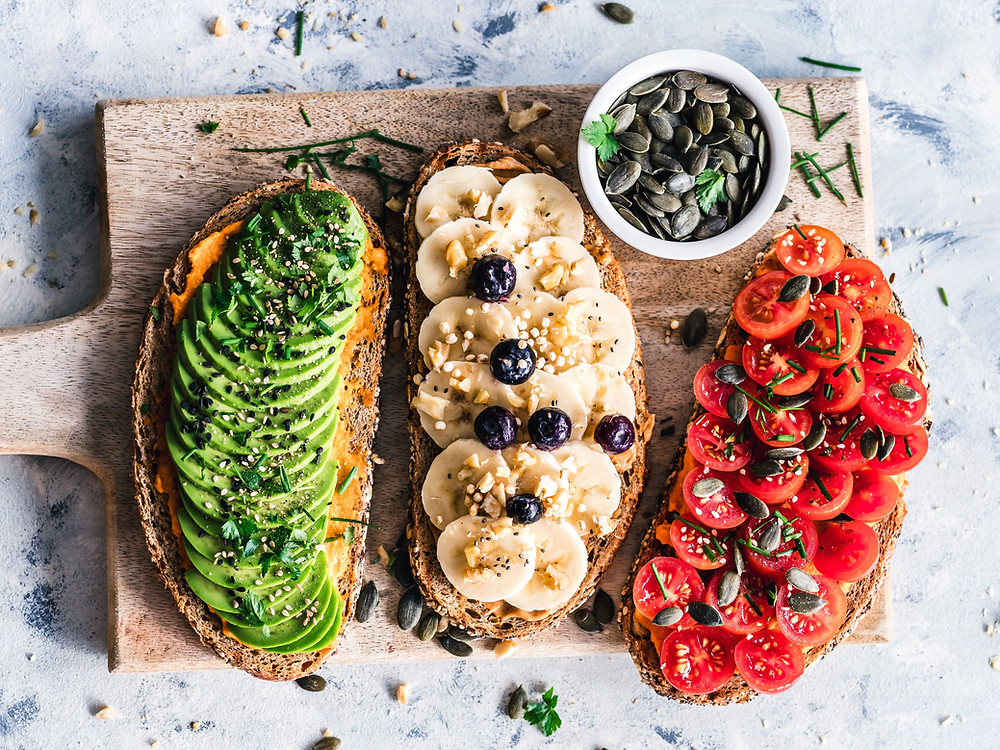 photo shows three slices of bread on a board with a side of pumpkin seeds. One slice is green avocado, another is yellow banana with blueberries and the last is read tomatoes with sauce on.