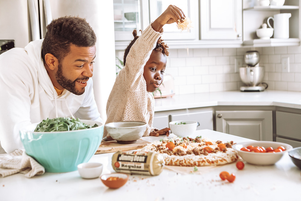 Father and son making pizza in the kitchen