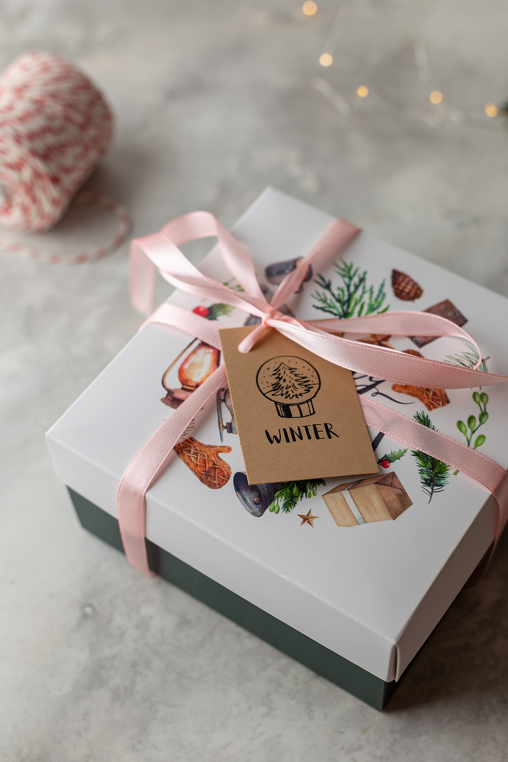 Box wrapped up with pink ribbon and a label on that says Winter