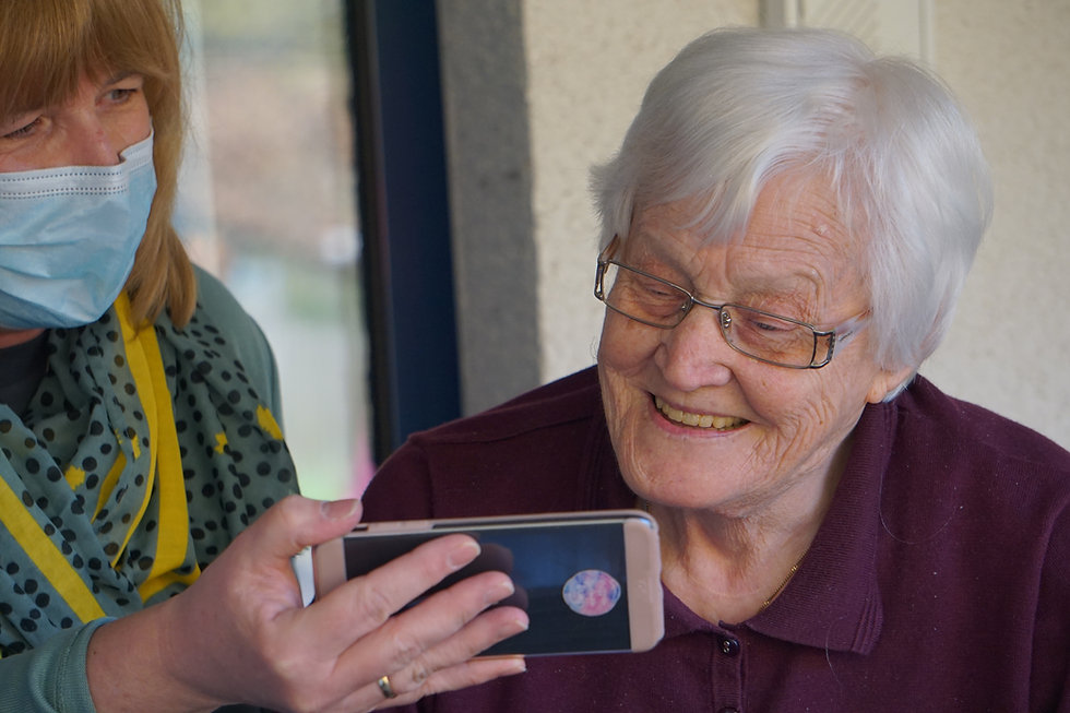 Image of caregiver showing smartphone photos to elderly woman.