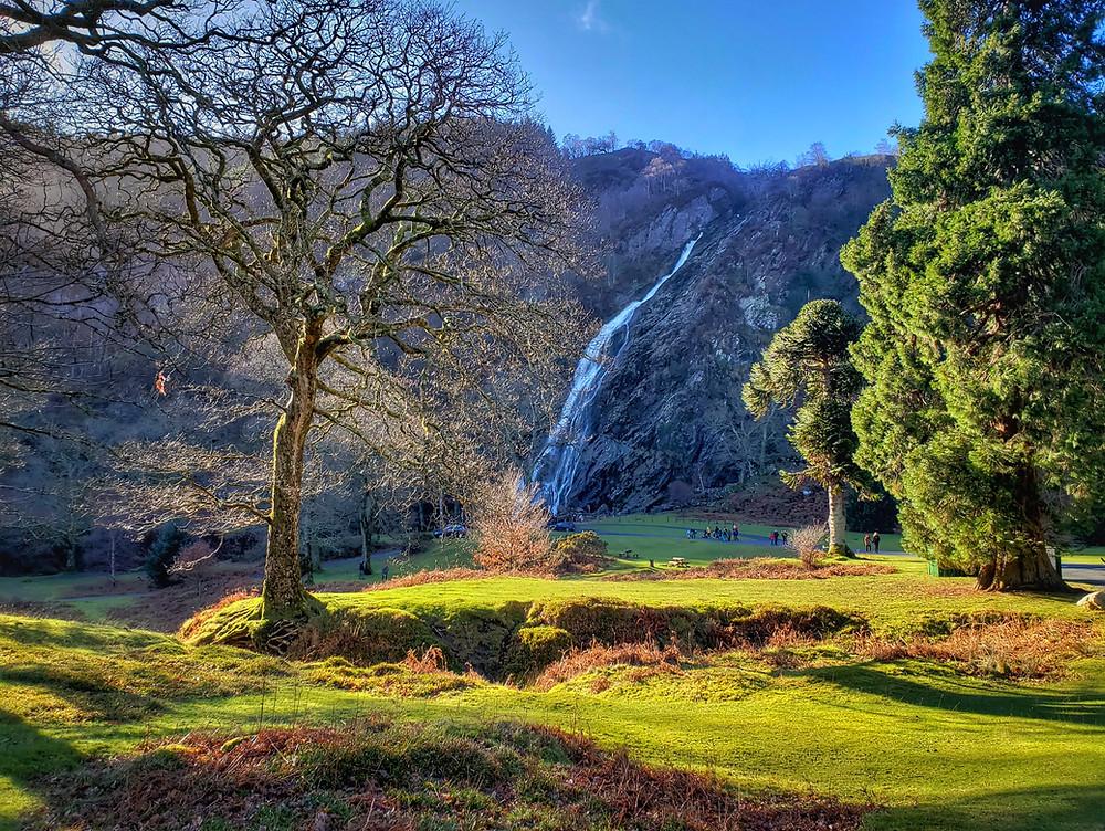 Waterfall gshing down a mountain side on a sunny day, a few people walking beside it