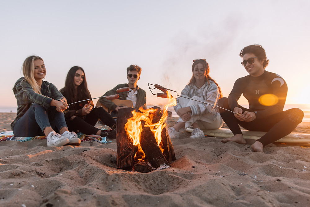5 young adults sitting on the beach at the end of summer. They are smiling and laughing while cooking hotdogs over a fire.