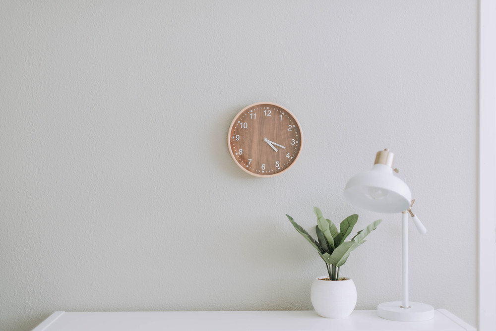 A single lamp and plant on a desk with a clock on the wall