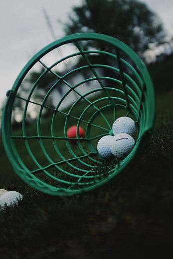 White golf balls sitting in the bottom of a green basket. Image by Matt Aylward