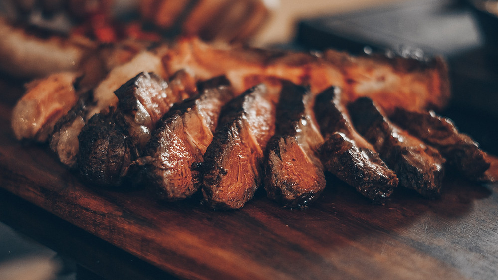 perfectly cooked and sliced steak fanned out on a cutting board