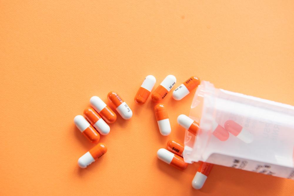 A bottle of prescription pills spilled on a bright orange table.