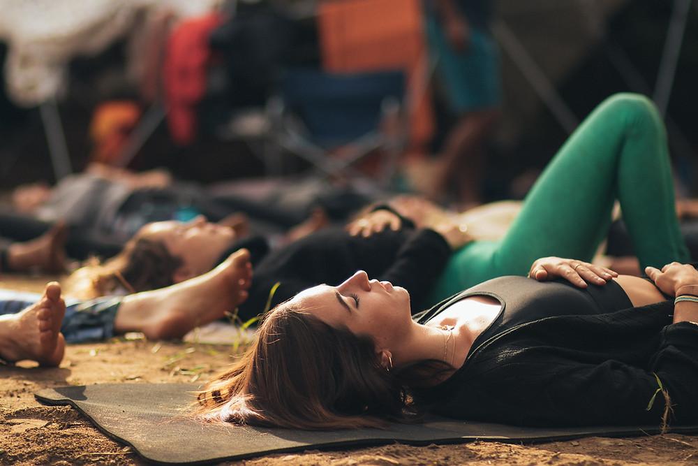 women lying on their backs with eyes closed practicing breathwork meditation