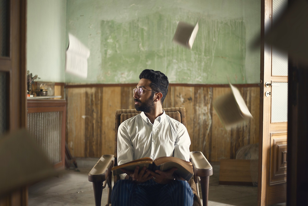 confused man sitting while books fly around his head