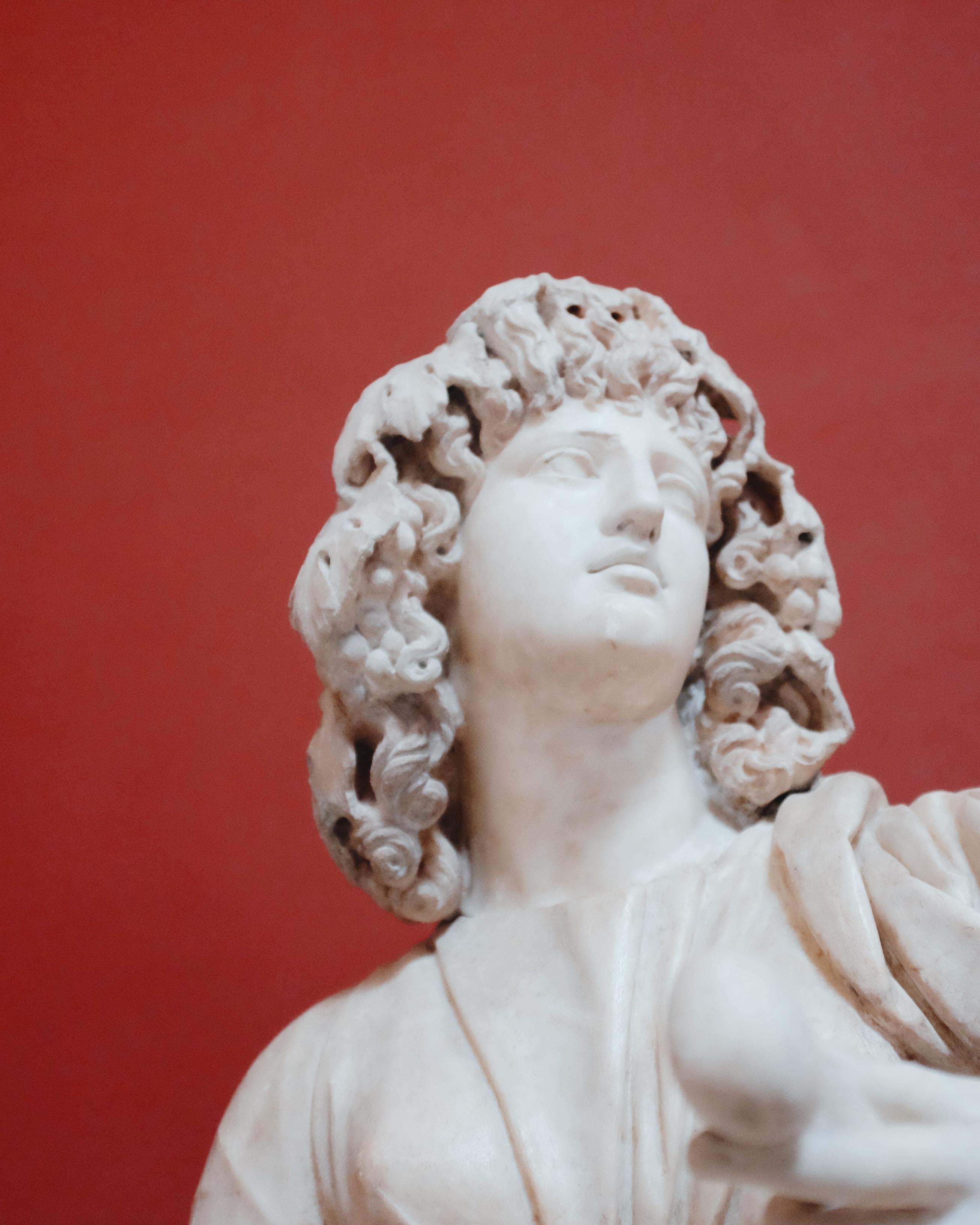 Estátua antiga de rosto de mulher com fundo vermelho.
