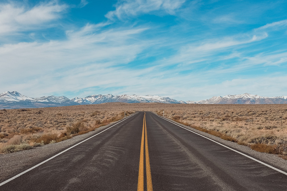 A road with mountains in the background.