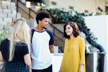 Two teenage girls talking to a teenage boy outside near some steps