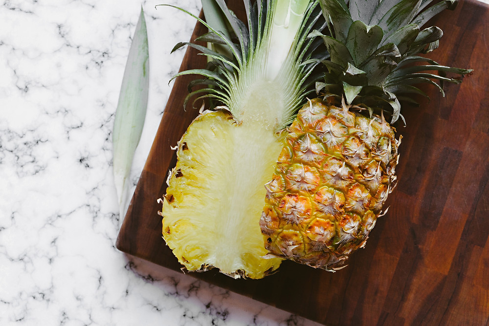 fresh pineapple sliced vertically on a wooden cutting board, resting on a marble countertop