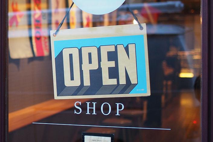 foto de uma loja com uma placa de aberta