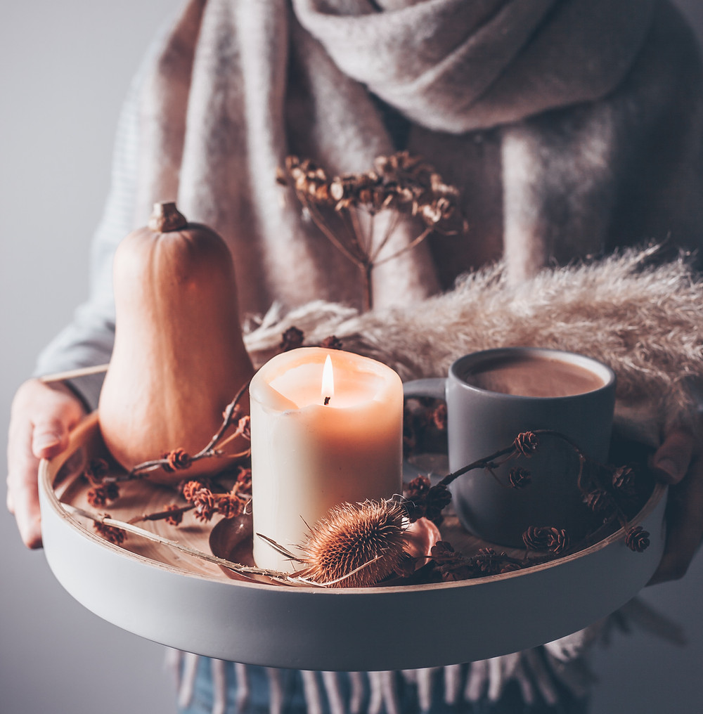 Person holding some autumn candles, Image from Unsplash