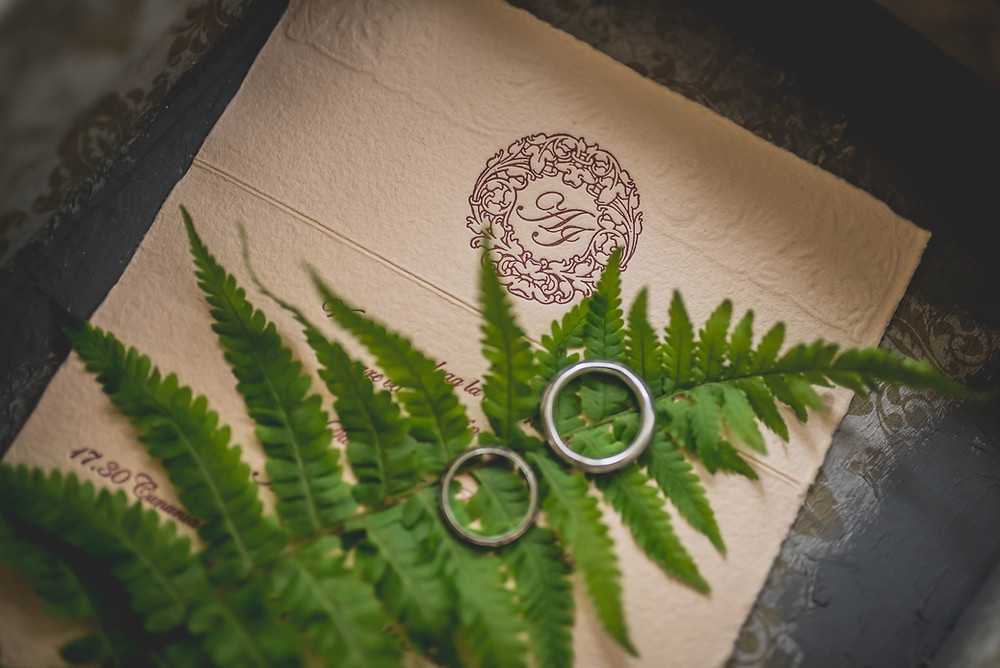 wedding invitation with a fern and wedding rings laying over it