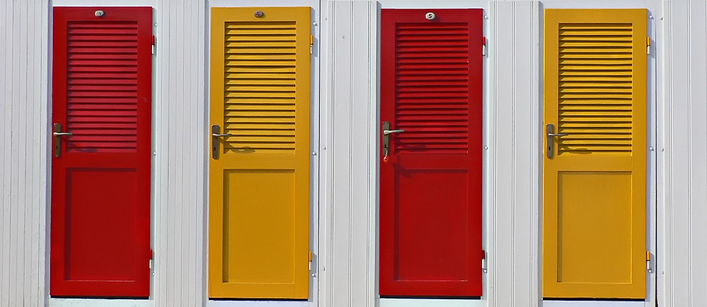 4 home entry doors next to each other on wall. left to right colores: red, yellow, red, yellow