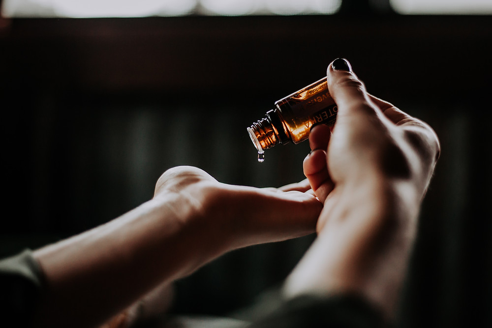 essential oil being poured out of the bottle onto a woman's hand