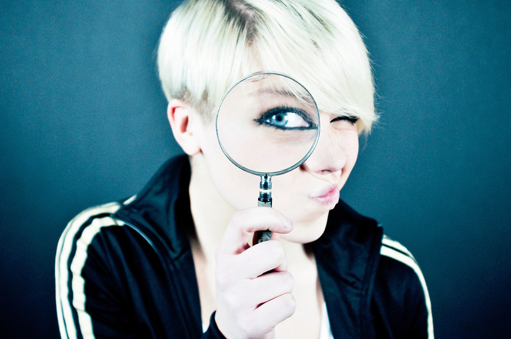 A woman looking through a magnify glass.