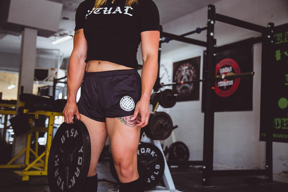 אישה שרירית עם מכנסיים קצרים מחזיקה משקולת בחדר כושר