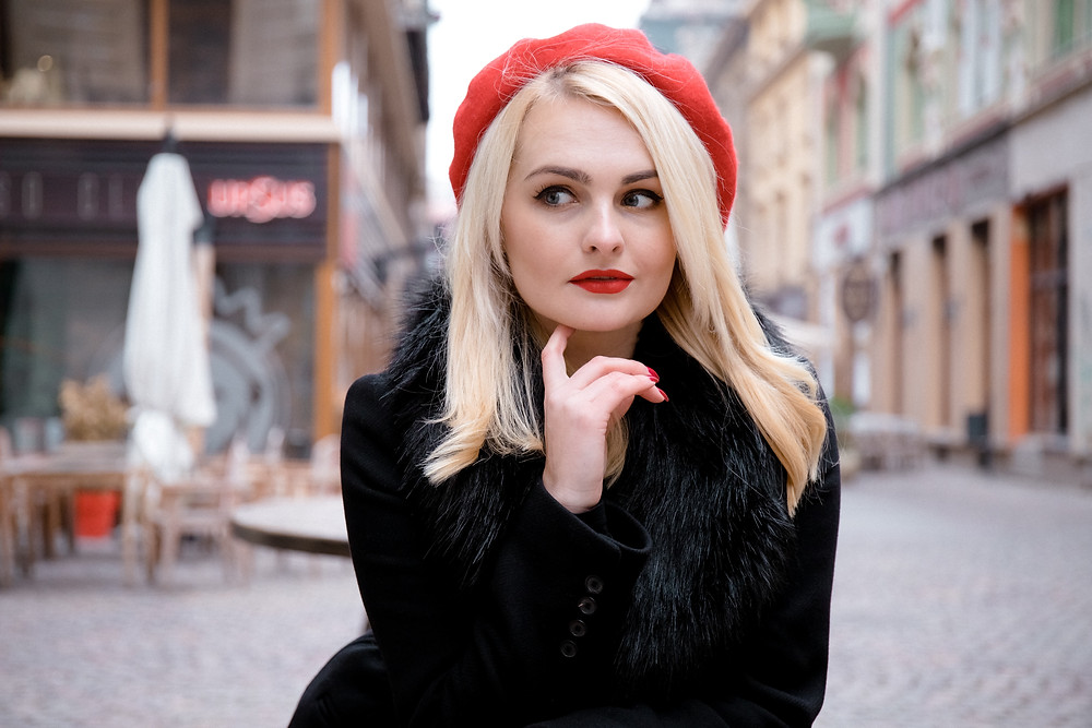 Close up of young woman in red beret in thoughtful pose