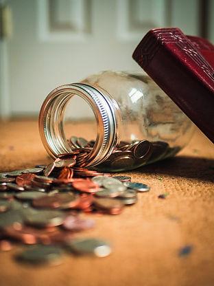 umgekipptes Glas mit Münzgeld