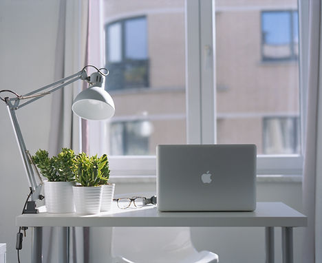 A light and airy home office with a desk in front of a window, a lamp, a plant, and a laptop.