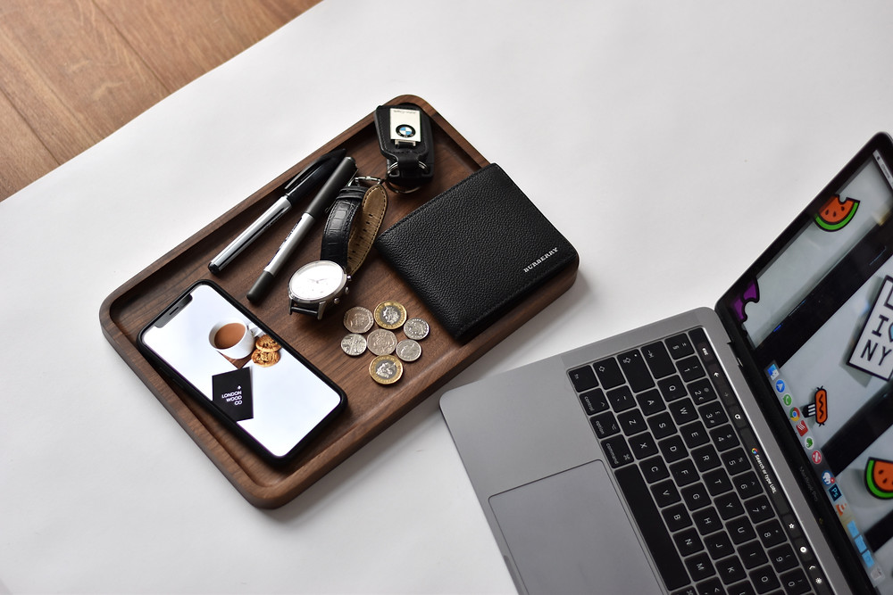 Tray on desk with phone, keys, watch, and wallet.
