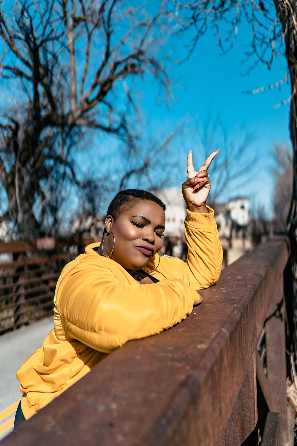 A black woman leans on a bridge railing wearing a yellow jacket, making the peace sign