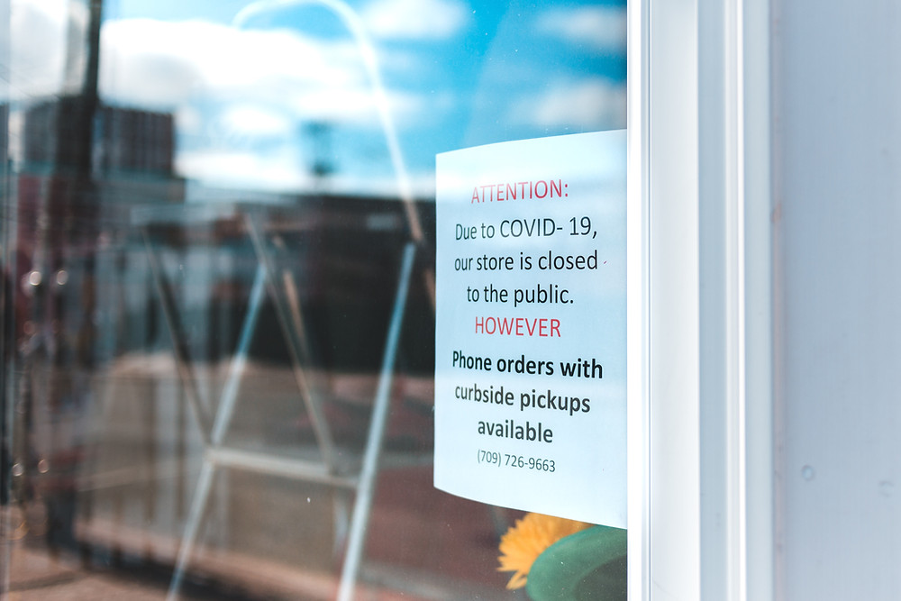 "A store window sign reads, ""Attention, due to Covid-19 our store is closed to the public, however, phone orders with curbside pickups available."""