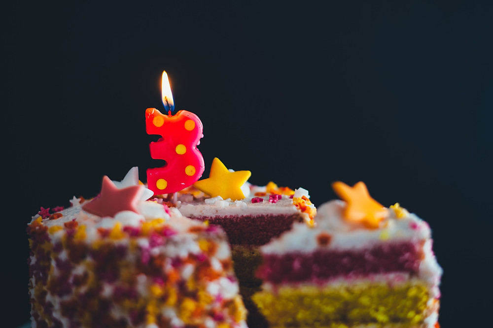 A colorful birthday cake with a lit number three candle on it