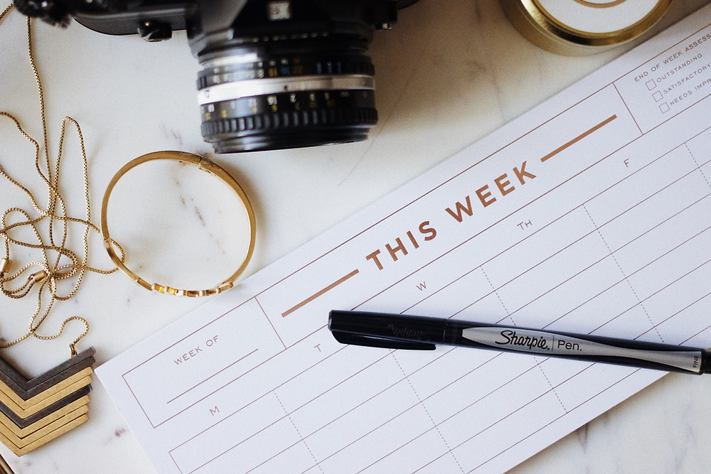 Photo of weekly planner with sharpie pen, camera and bracelet